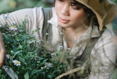 jeune femme coupe au sécateur plants de fleurs de son jardin